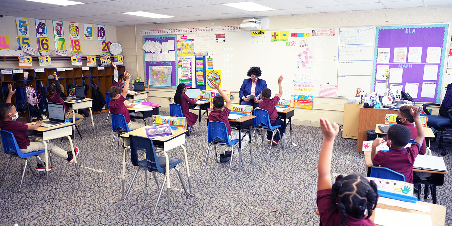 Teacher reading at front of classroom and students sitting at desks with hands raised.