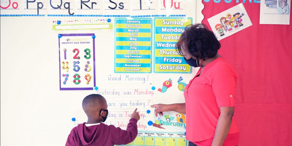 Teacher and student pointing to words on a white board at the front of the class.