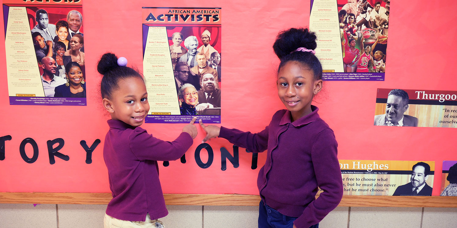 Smiling students standing and pointing to an African American Activists poster in school hallway.