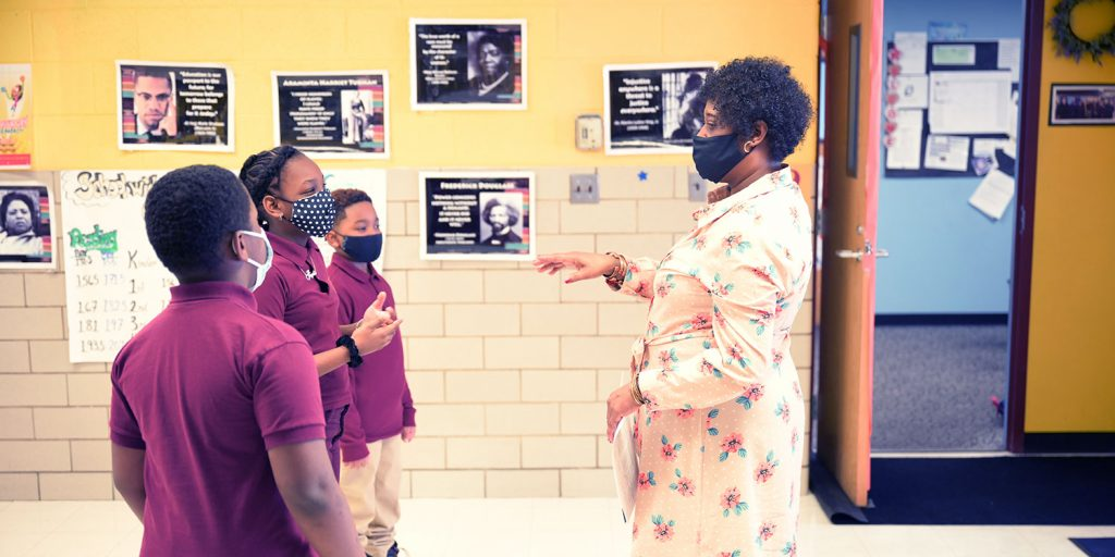 Masked staff member and students in school hallway.