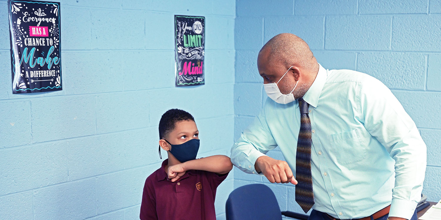 Masked Mr. Shawn Hurt, Head of School, touching elbows with a masked student.