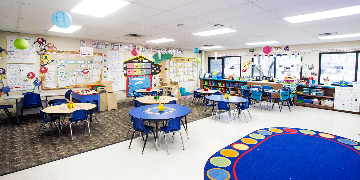 Elementary classroom with bright rug, reading nook and round tables.
