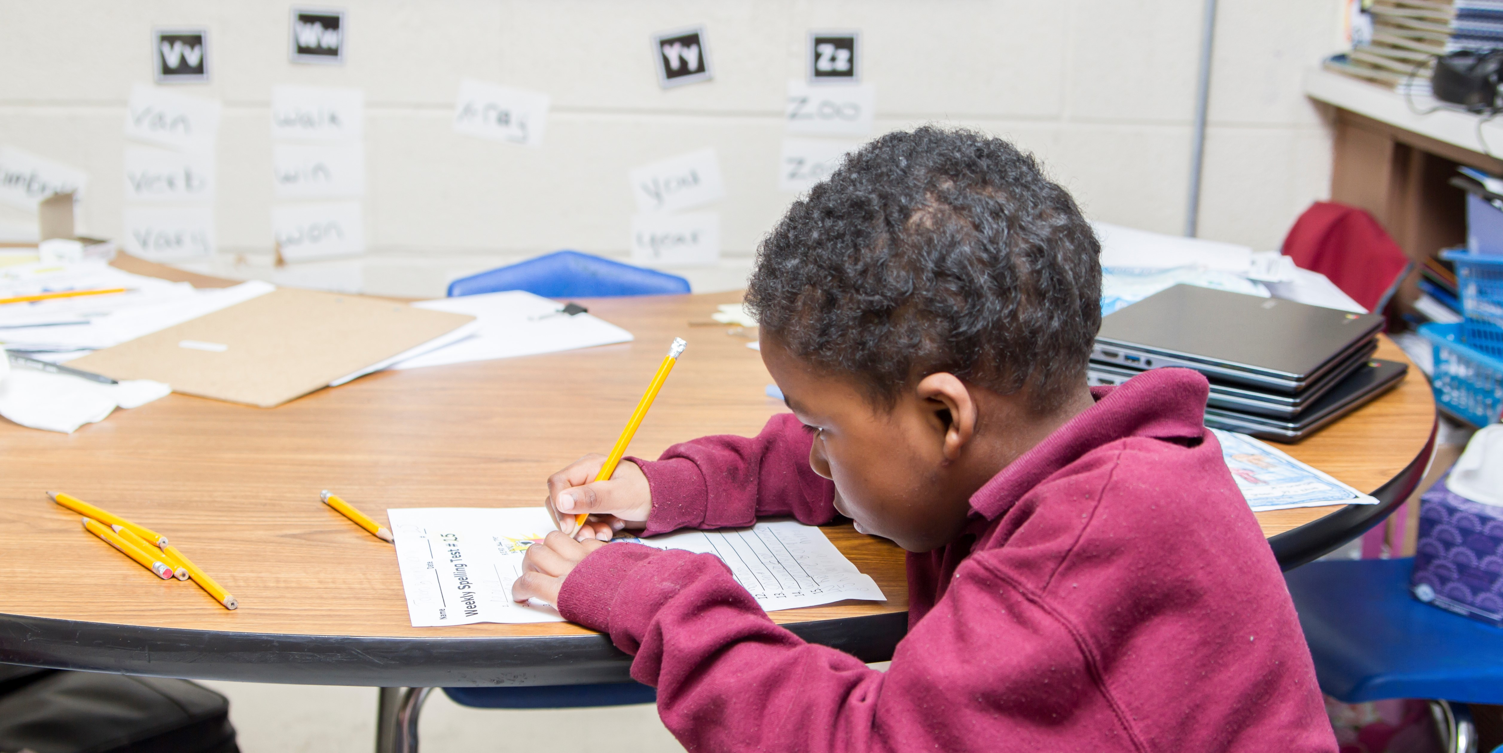 Child working at desk in classroom.