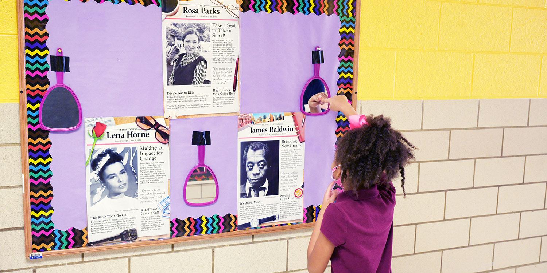 Student looking in mirror on bulletin board.